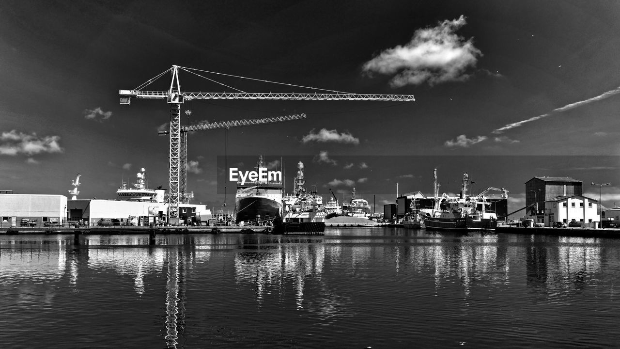Crane and boats at harbor on sea against sky