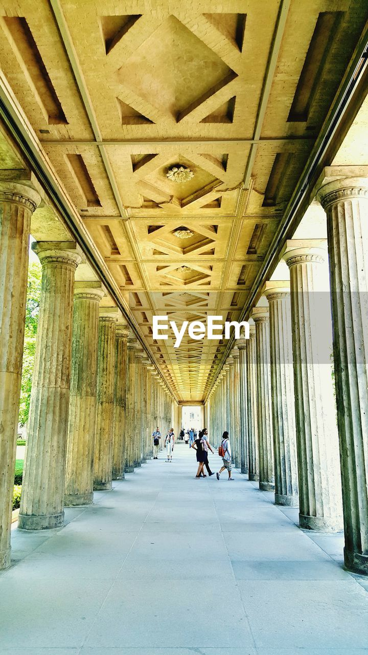 architecture, built structure, direction, the way forward, ceiling, arcade, indoors, corridor, architectural column, real people, building, incidental people, diminishing perspective, day, walking, lighting equipment, transportation, in a row, colonnade, vanishing point, long