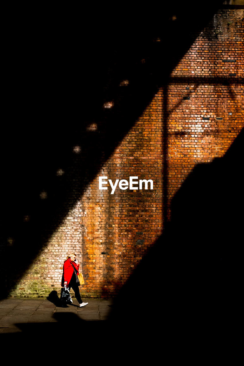 full length, real people, architecture, one person, lifestyles, night, transportation, built structure, men, shadow, sport, city, street, illuminated, motion, unrecognizable person, walking, wall - building feature, outdoors, dark, riding