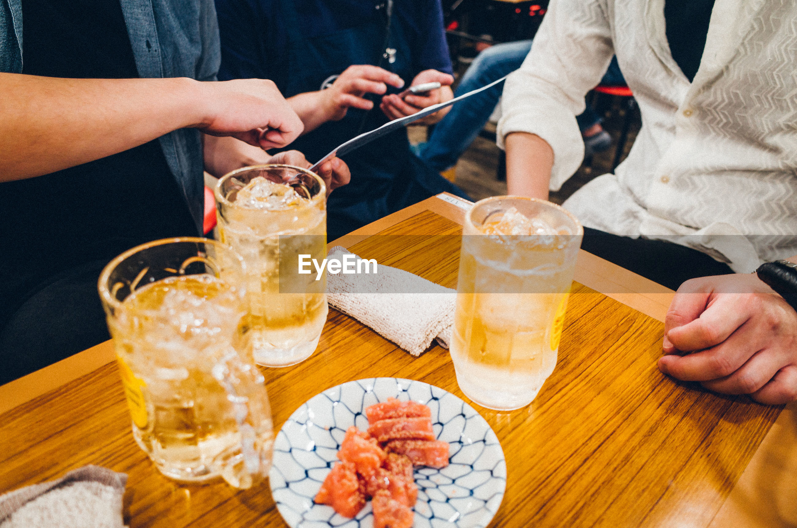 Midsection of male friends having food and drinks at table in restaurant