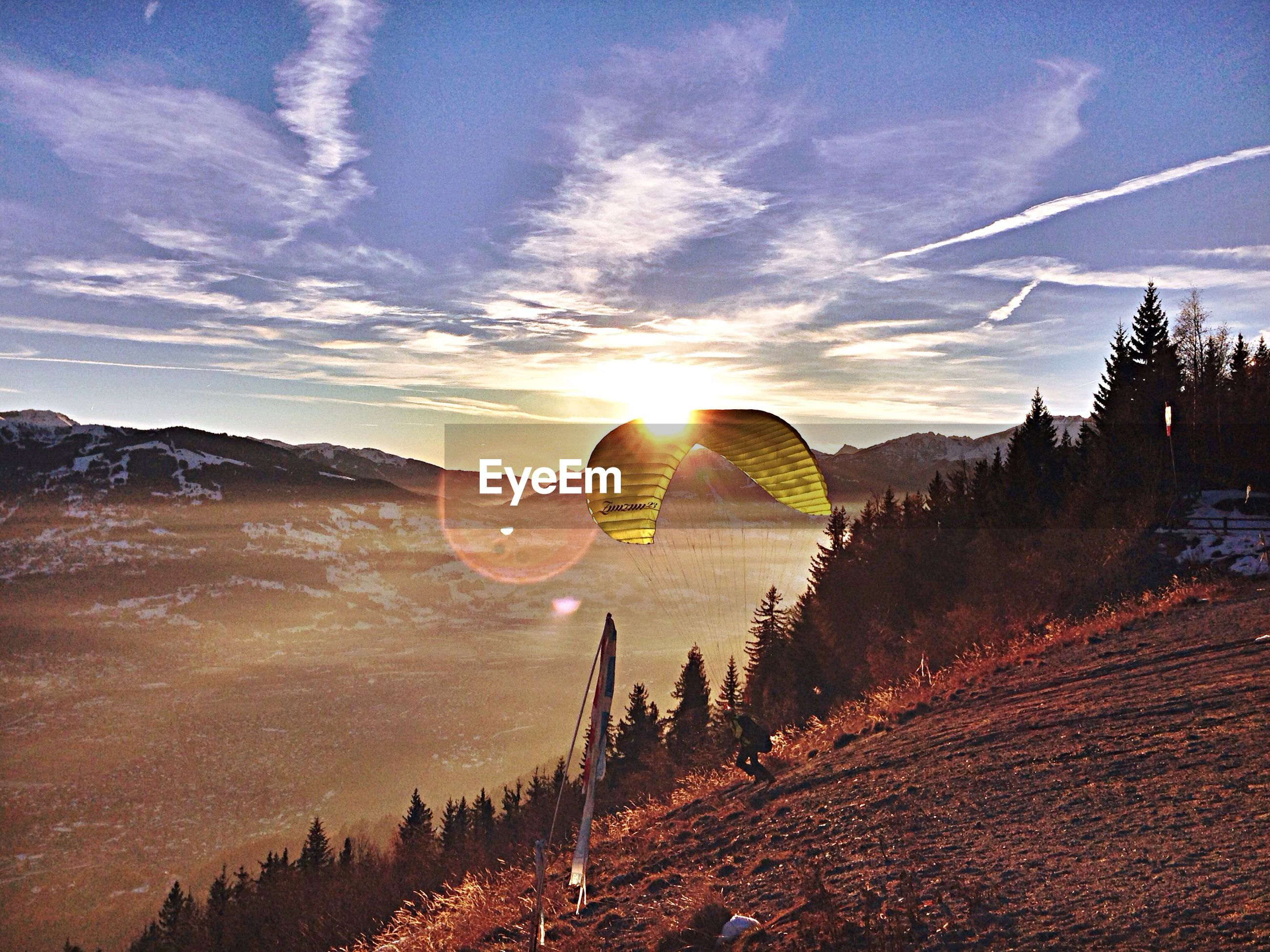 Person paragliding from mountain against sky