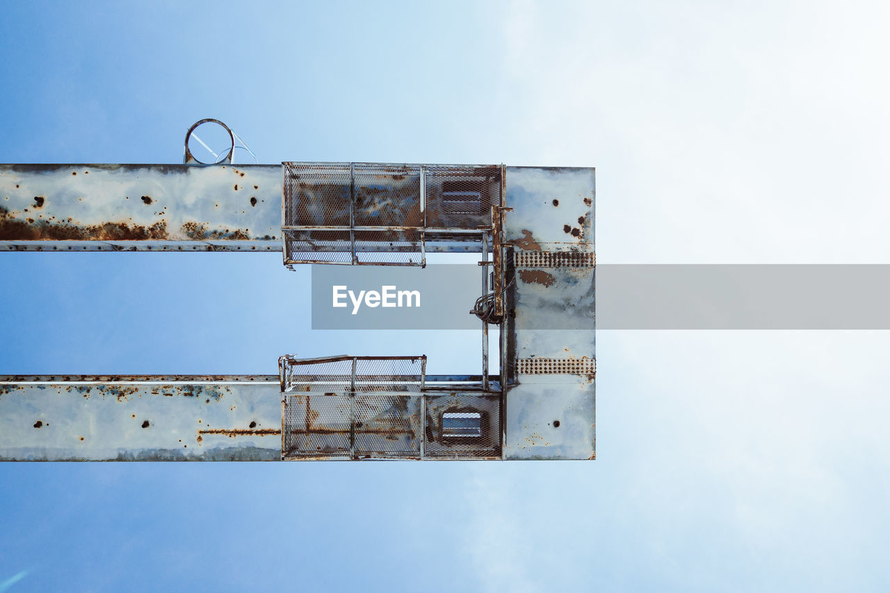 sky, low angle view, metal, rusty, day, architecture, nature, abandoned, no people, industry, outdoors, built structure, old, damaged, run-down, blue, deterioration, decline, obsolete, machinery, ruined, construction equipment