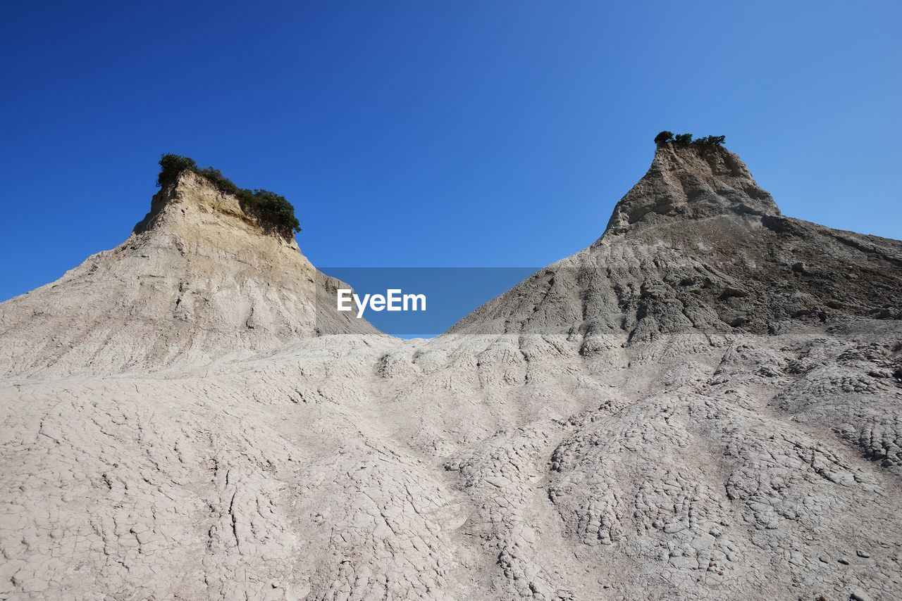 sky, clear sky, scenics - nature, beauty in nature, rock, mountain, tranquil scene, tranquility, nature, non-urban scene, rock - object, rock formation, landscape, low angle view, physical geography, geology, environment, no people, land, blue, mountain range, outdoors, arid climate, climate, mountain peak, formation, eroded