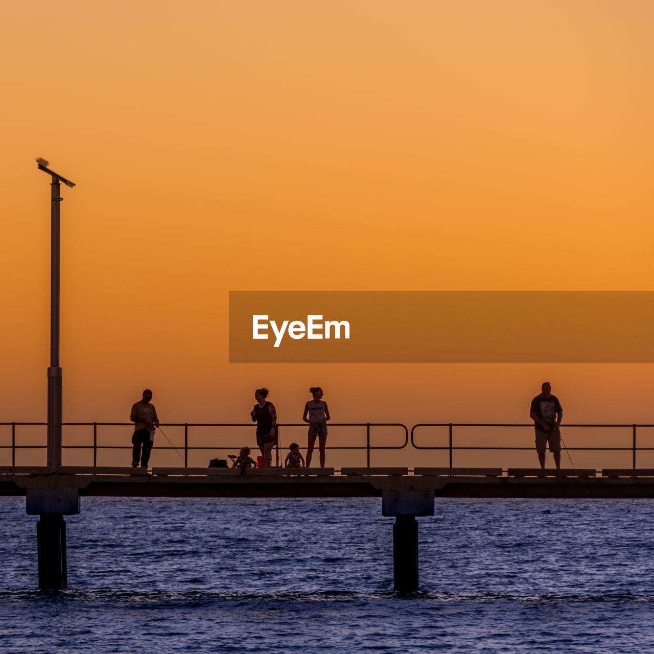 water, orange color, sunset, sky, silhouette, sea, group of people, real people, beauty in nature, scenics - nature, lifestyles, waterfront, nature, men, clear sky, copy space, architecture, standing, built structure, outdoors, horizon over water, bridge - man made structure, sun