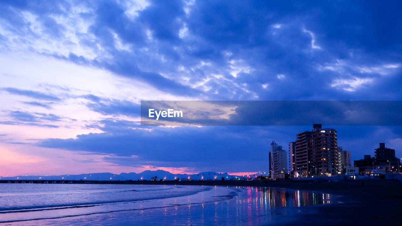 ILLUMINATED MODERN BUILDINGS BY SEA AGAINST SKY AT DUSK