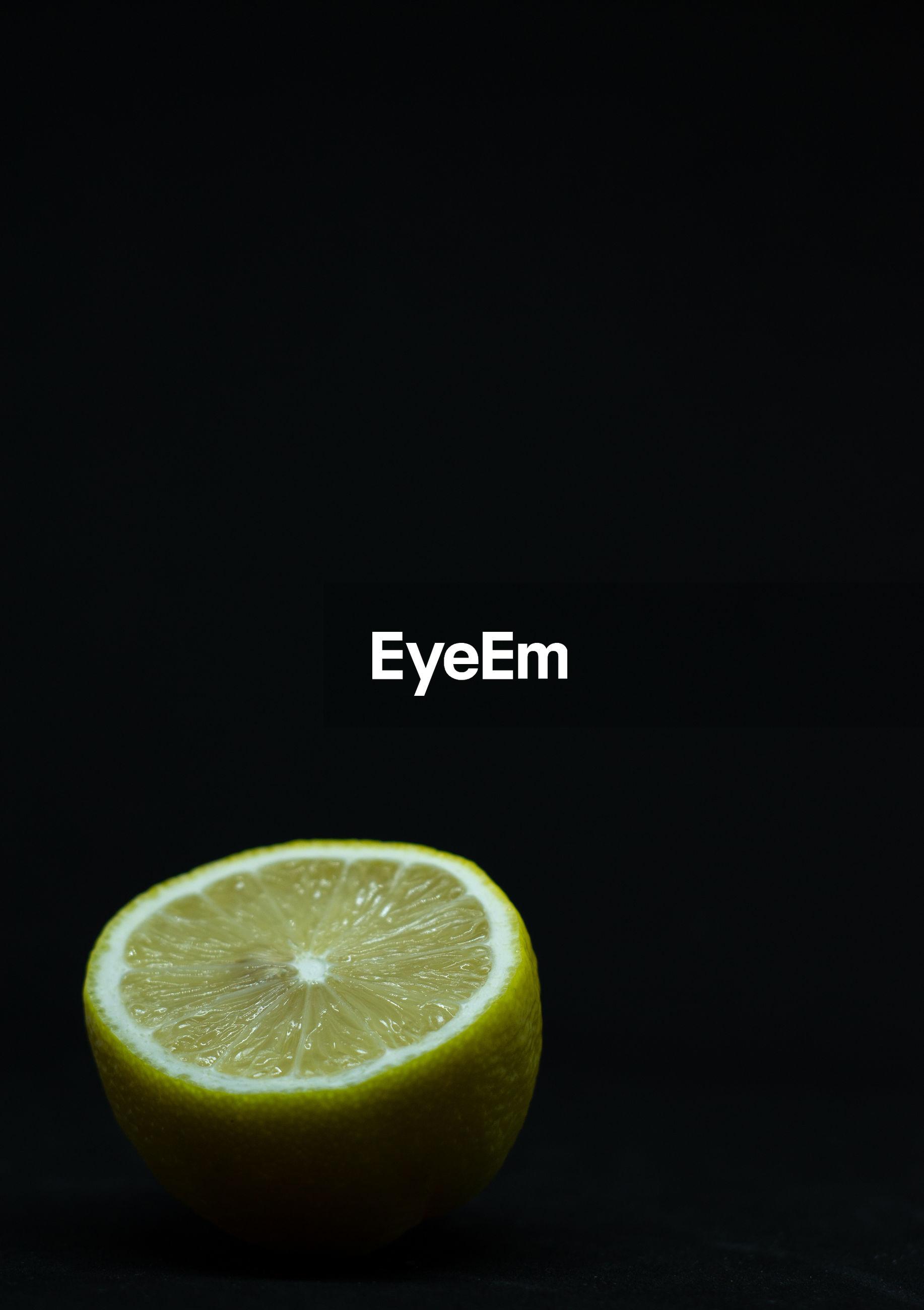 Close-up of lemon slice on table against black background