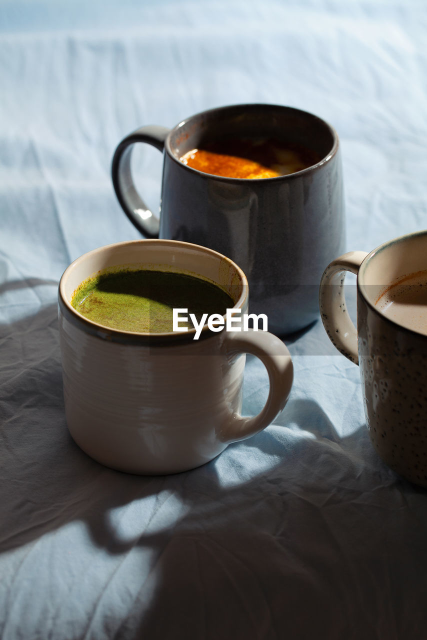 HIGH ANGLE VIEW OF COFFEE CUP AND TEA ON TABLE