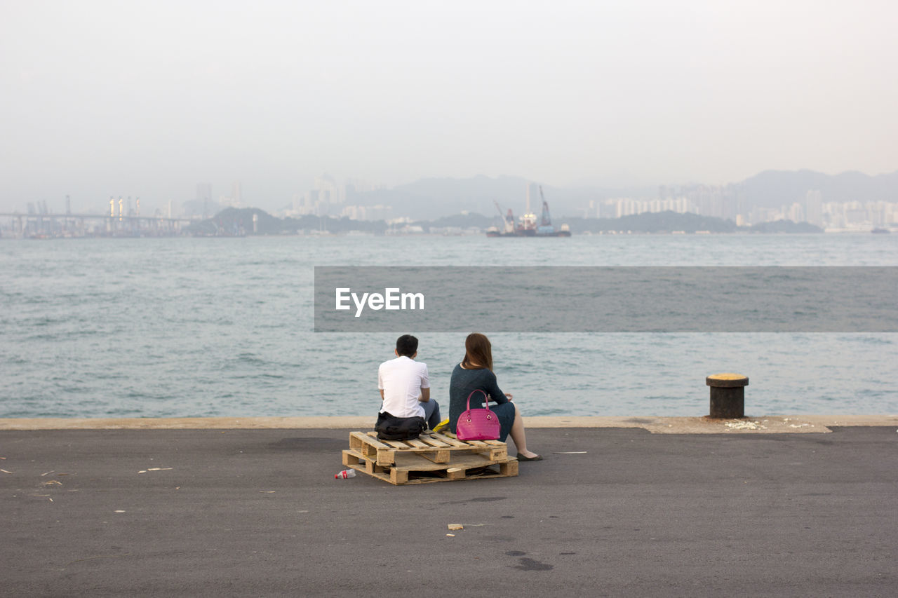 Rear View Of Couple Sitting On Promenade Against Clear Sky
