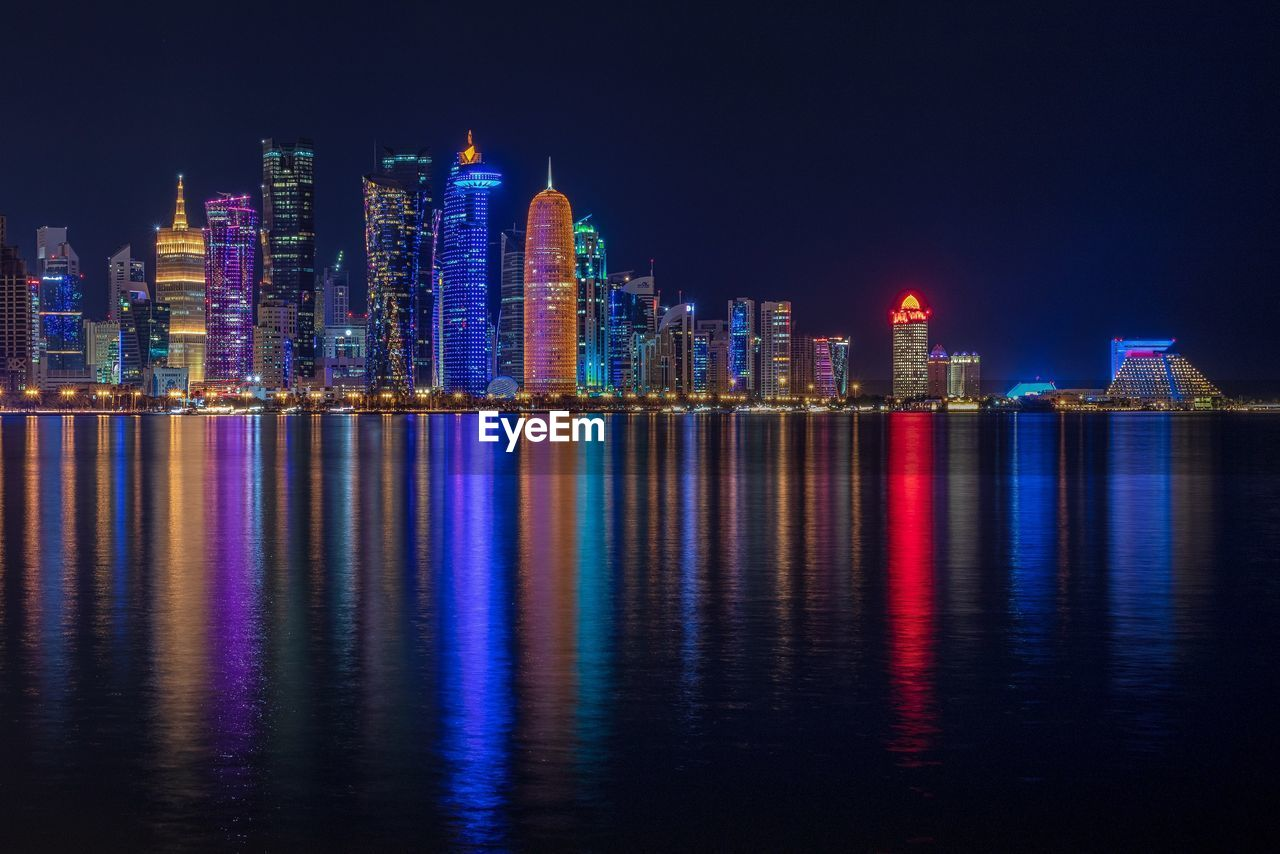 architecture, building exterior, water, built structure, waterfront, building, night, reflection, city, illuminated, office building exterior, urban skyline, skyscraper, cityscape, sky, landscape, sea, modern, tall - high, no people, outdoors, financial district, nightlife