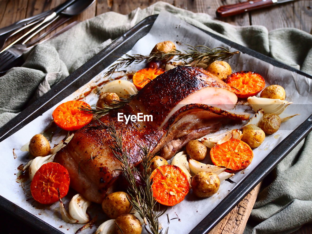 High angle close-up of roasted pork served in tray on table