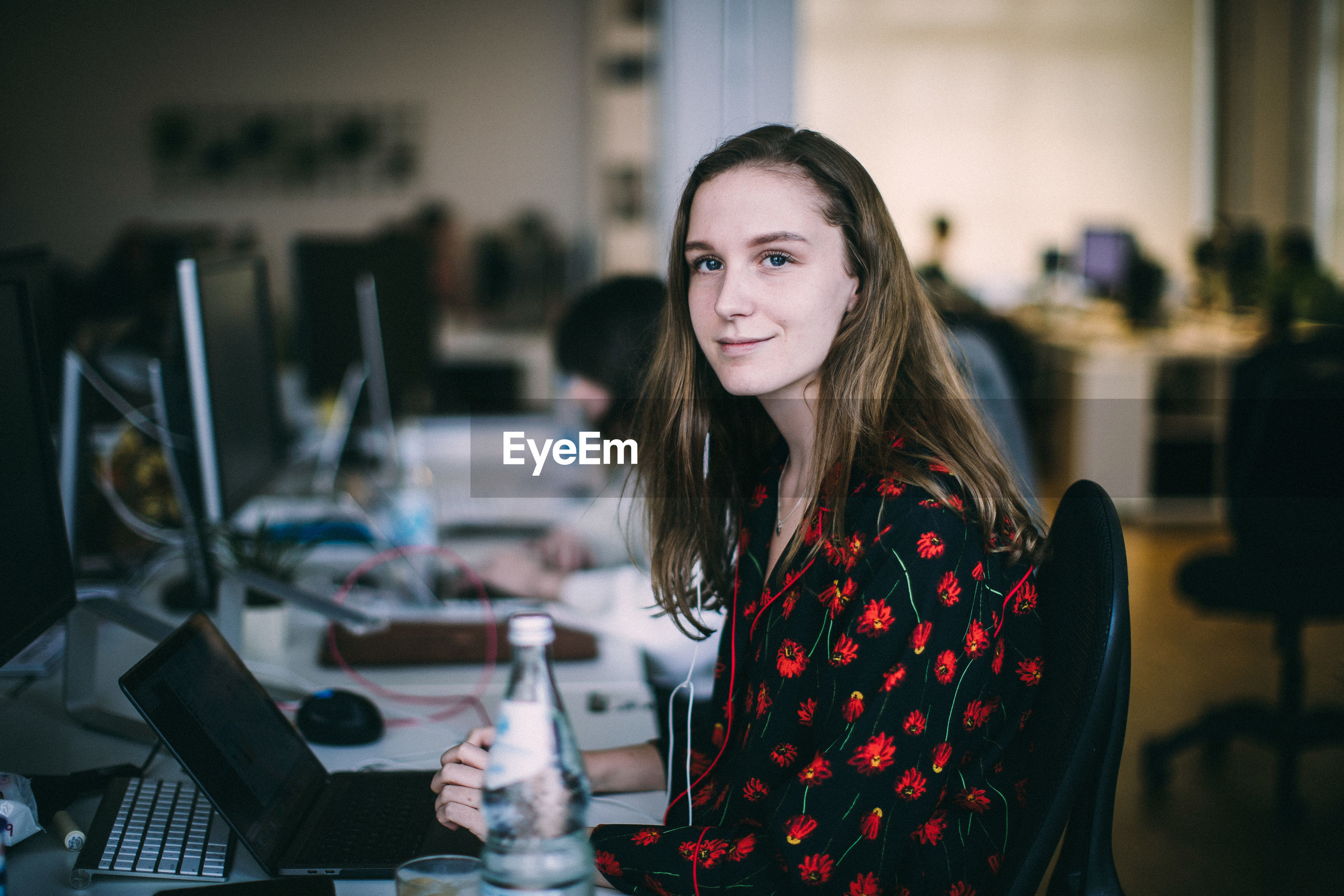 Side view portrait of young woman working at desk in creative office
