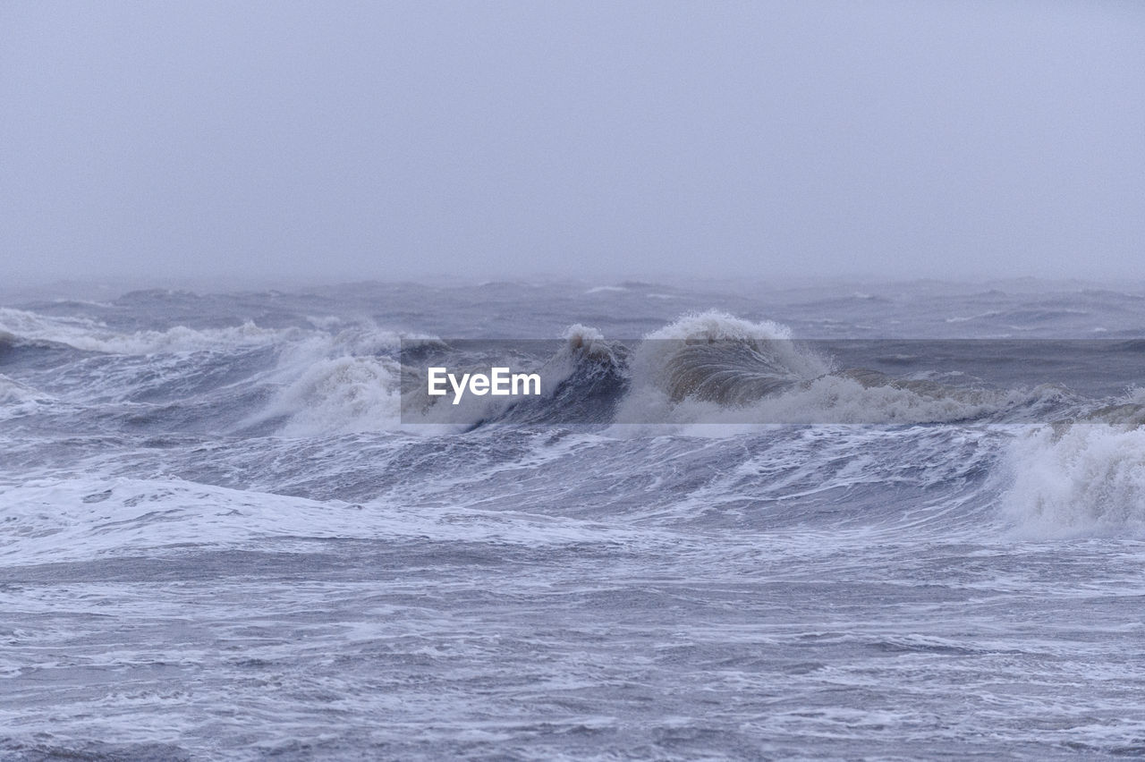 SCENIC VIEW OF WAVES IN SEA AGAINST CLEAR SKY