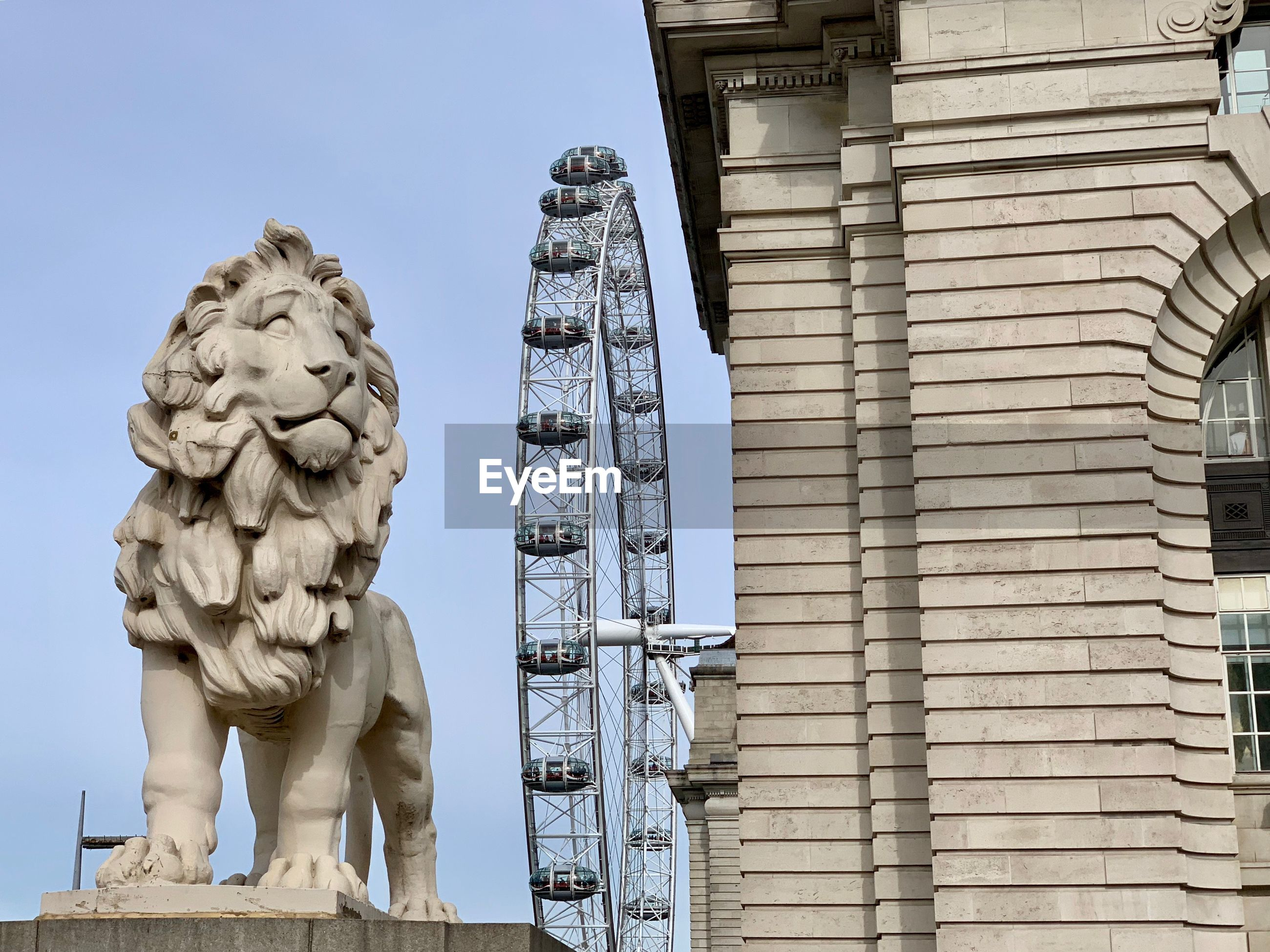 Low angle view of lion statue and millennium wheel by building against clear sky