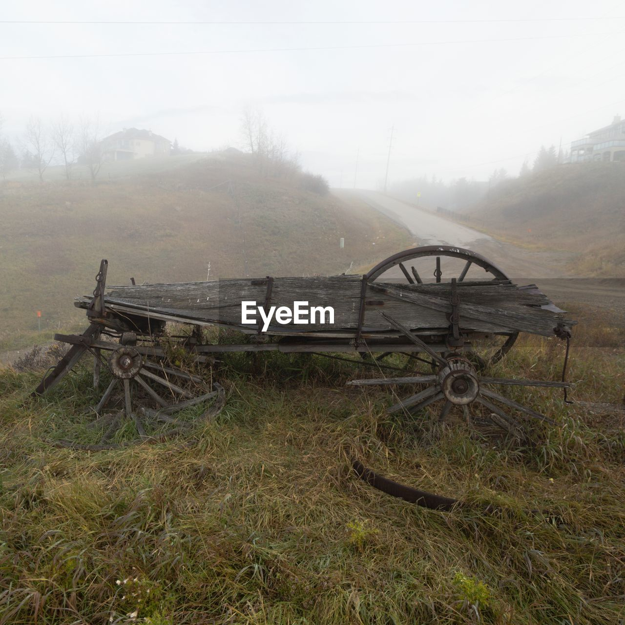 fog, land, transportation, field, nature, grass, abandoned, no people, day, landscape, mode of transportation, environment, sky, plant, tranquility, obsolete, scenics - nature, tranquil scene, beauty in nature, outdoors, wheel, deterioration