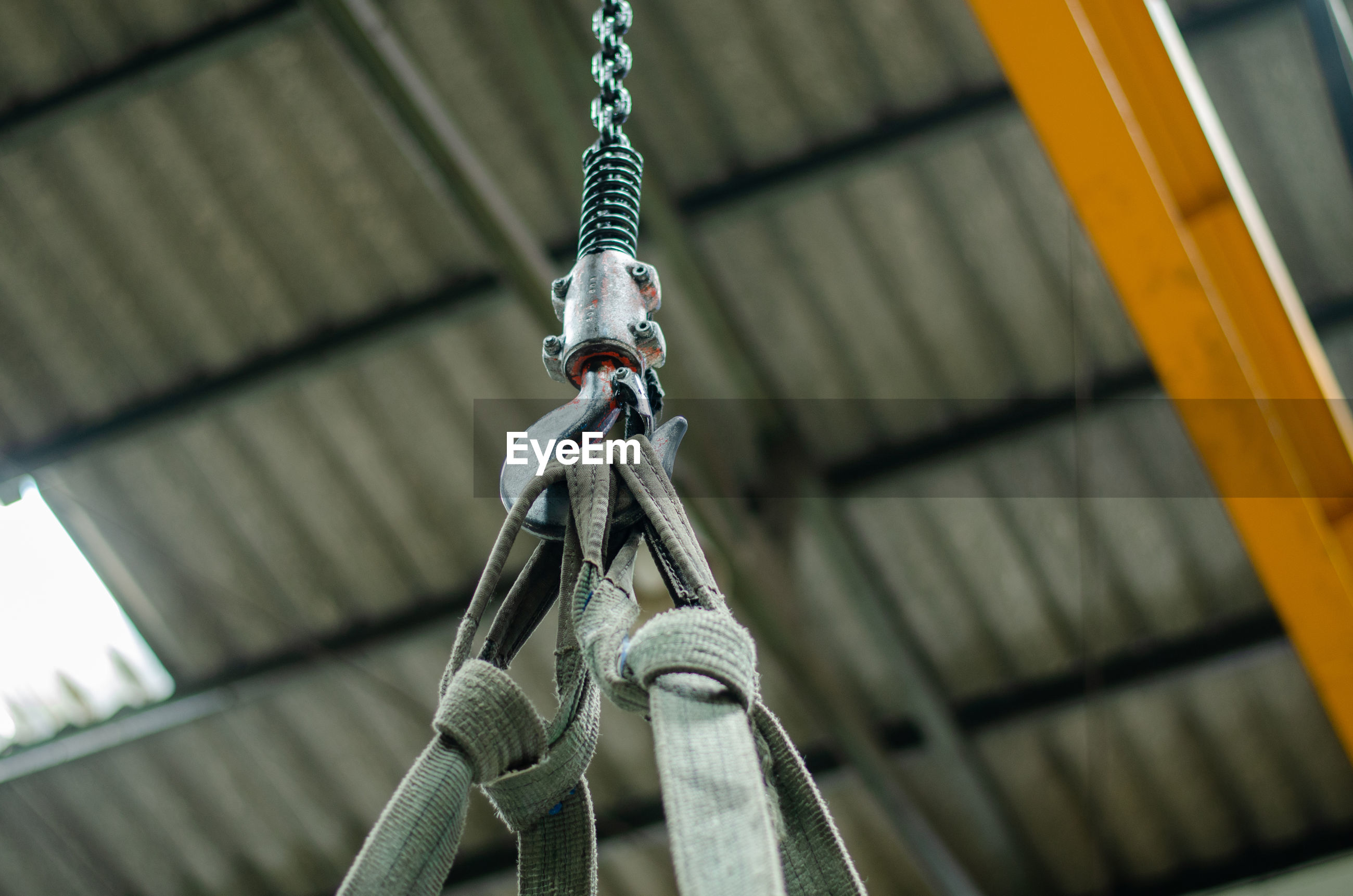 LOW ANGLE VIEW OF ROPE HANGING ON METAL