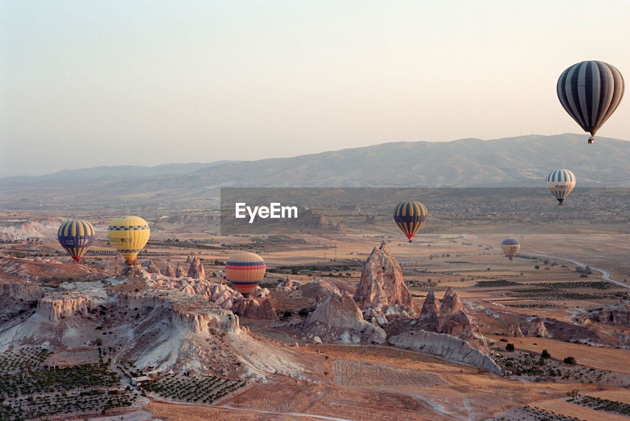 Hot Air Balloon Flying Over Landscape Against Clear Sky