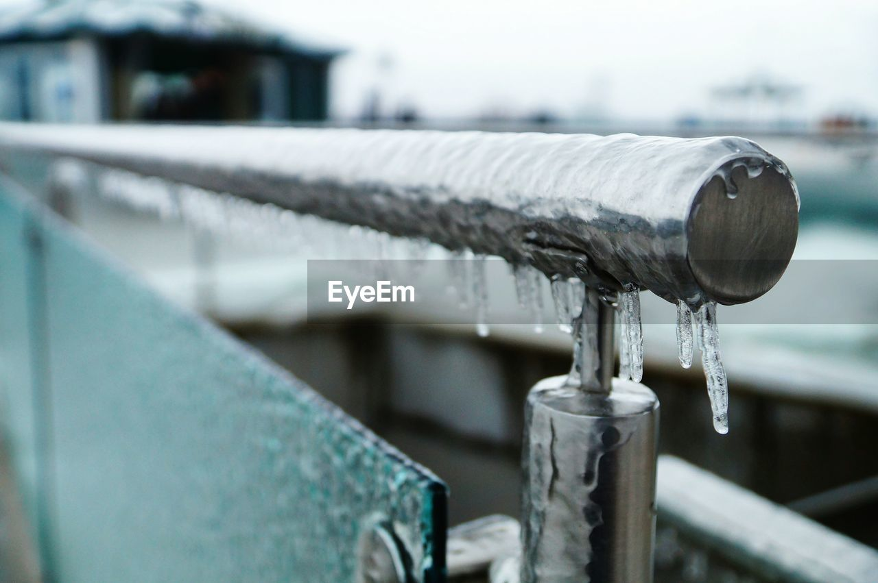 focus on foreground, close-up, winter, day, metal, water, cold temperature, no people, built structure, ice, railing, frozen, architecture, outdoors, snow, nature, motion, icicle, running water, silver colored, flowing, flowing water