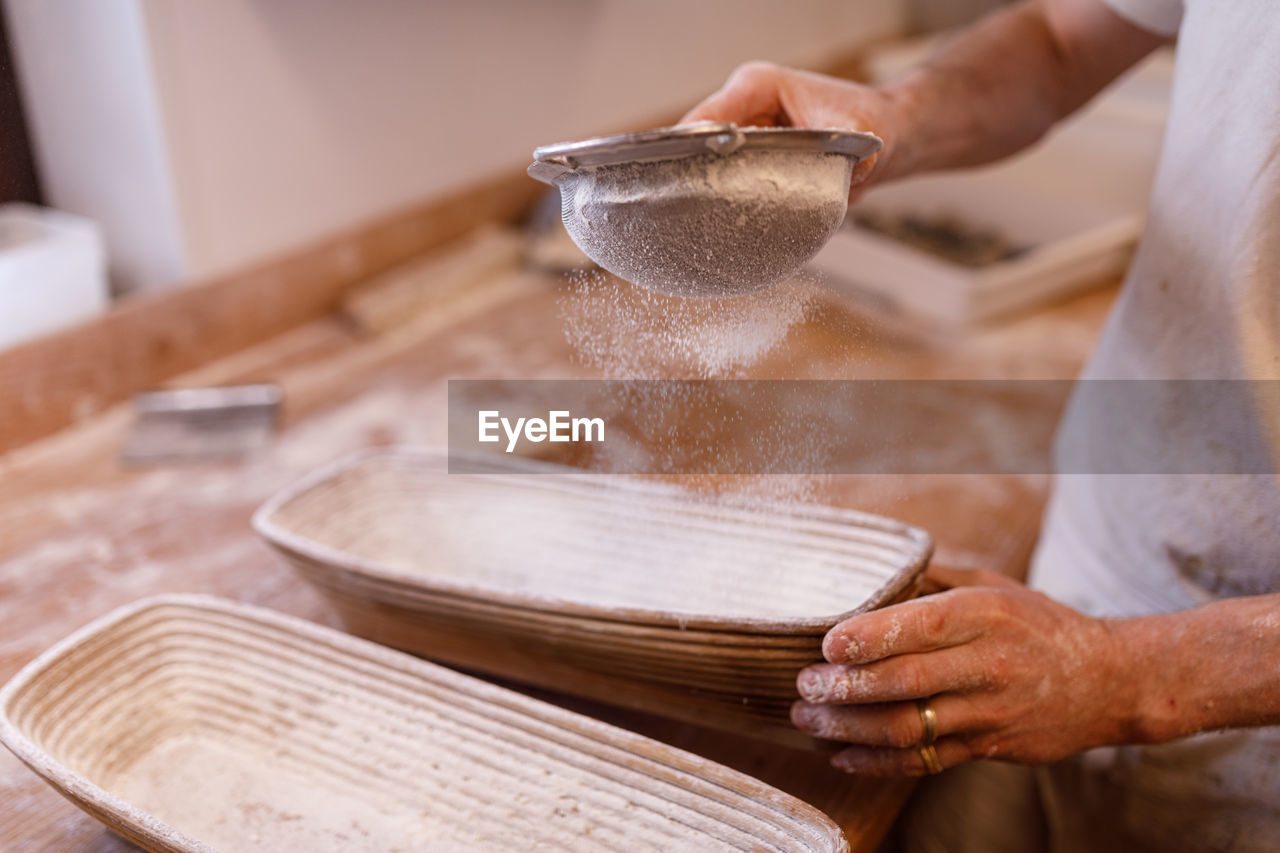 Midsection of man sieving flour