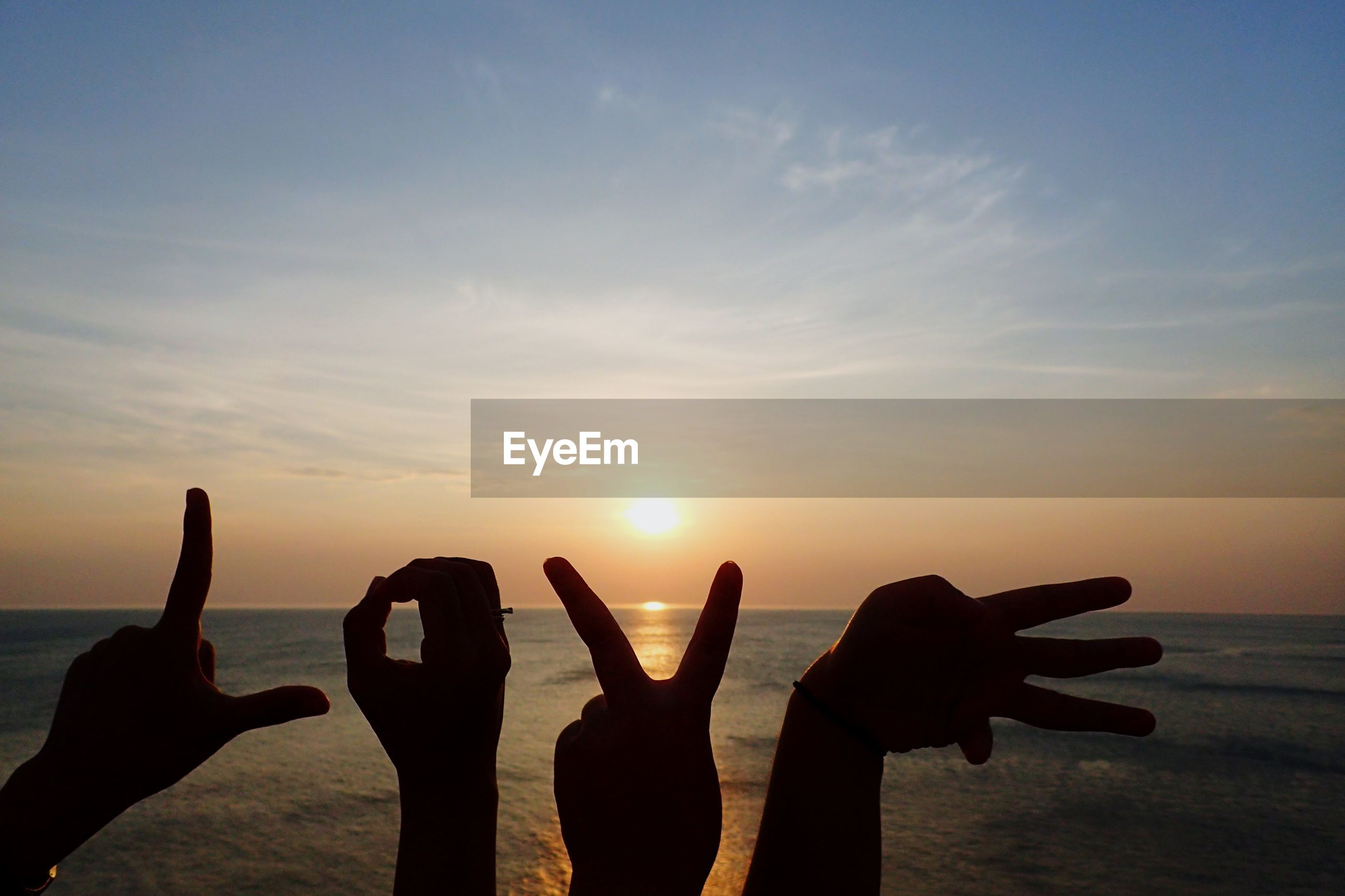 Silhouette hands making love text against sea during sunset