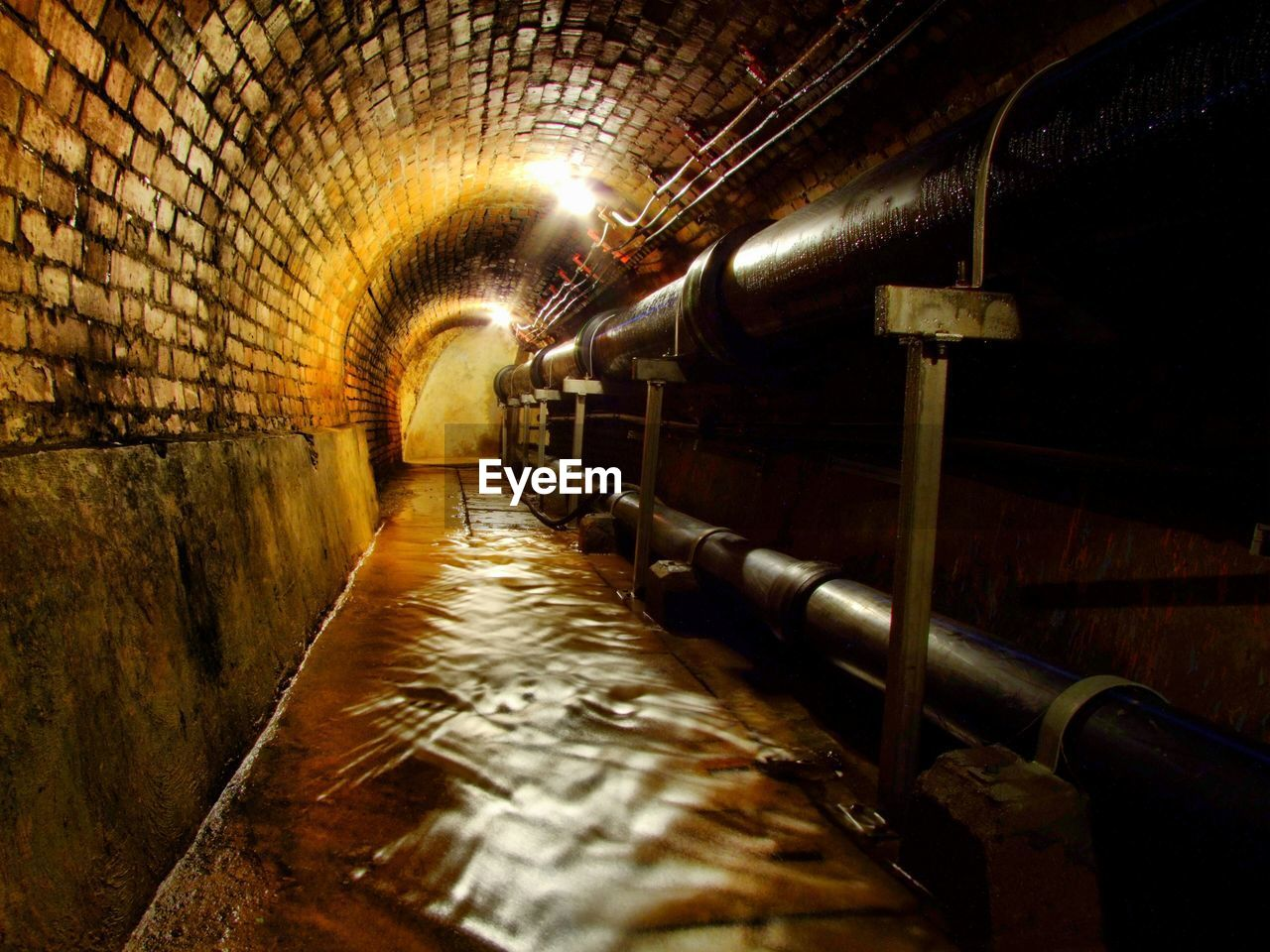 indoors, architecture, tunnel, illuminated, no people, pipe - tube, metal, lighting equipment, built structure, transportation, wall - building feature, water, flowing water, arch, public transportation, connection, subway, industry, blurred motion, flowing, ceiling