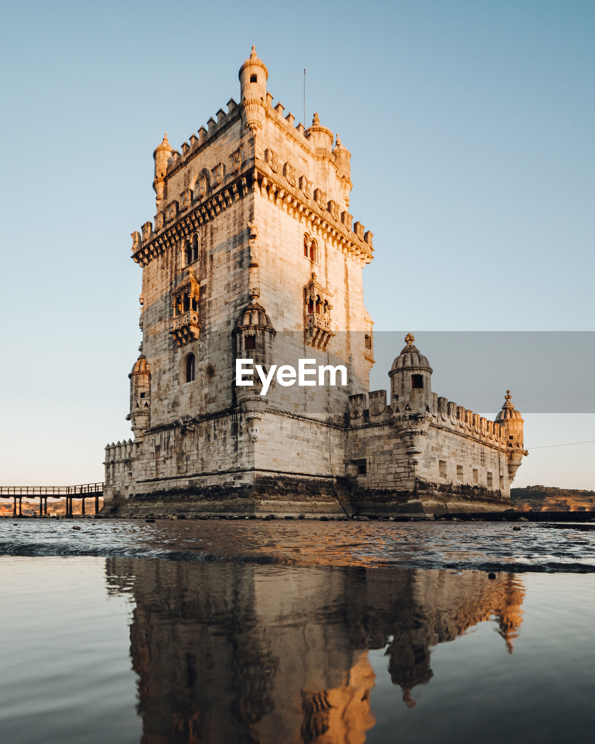 Low angle view of historic building by river against clear sky