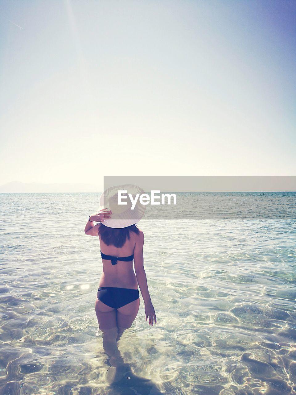 Rear view of bikini woman in sea against clear sky