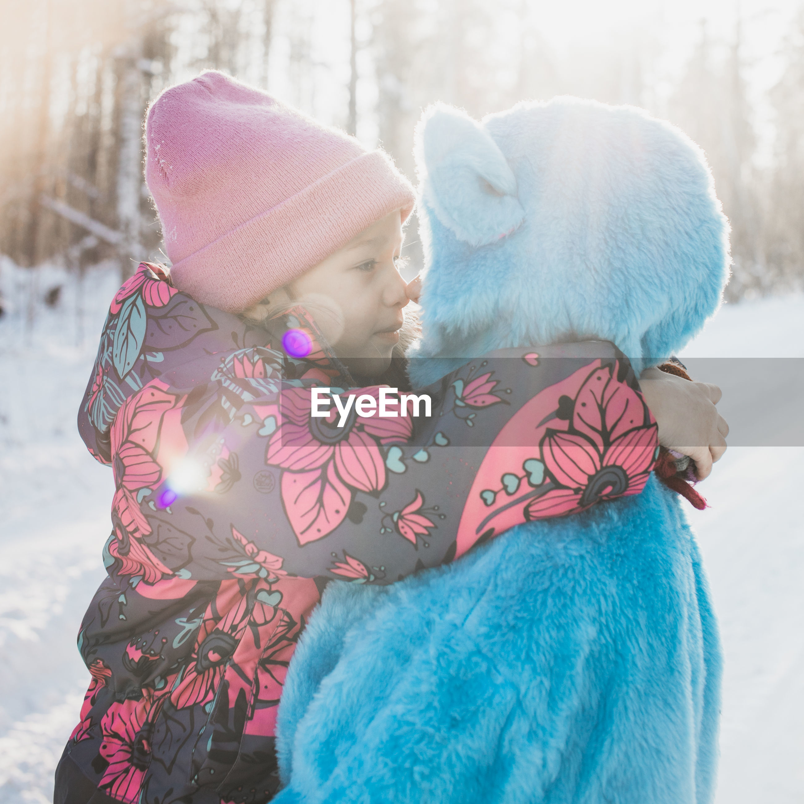 Father wearing costume with daughter on snowy field