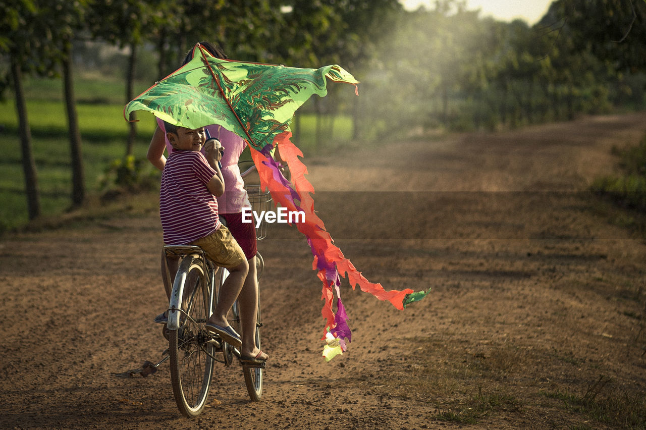 Rear view of friends riding bicycle while flying kite on land