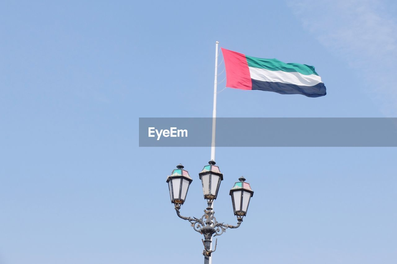 Low angle view of uae flag against blue sky