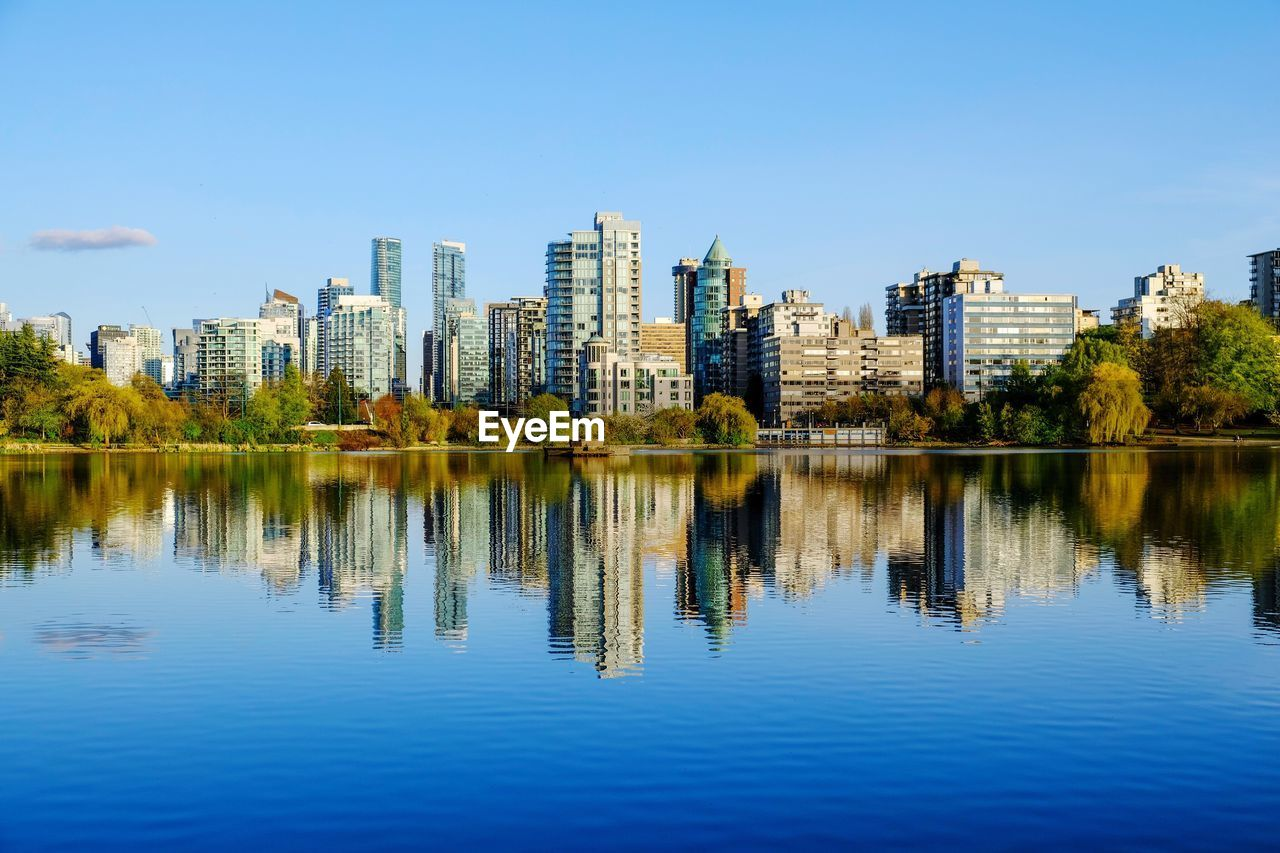 architecture, building exterior, water, reflection, built structure, sky, building, waterfront, city, office building exterior, nature, urban skyline, lake, landscape, skyscraper, no people, tree, blue, tall - high, cityscape, outdoors, modern, financial district