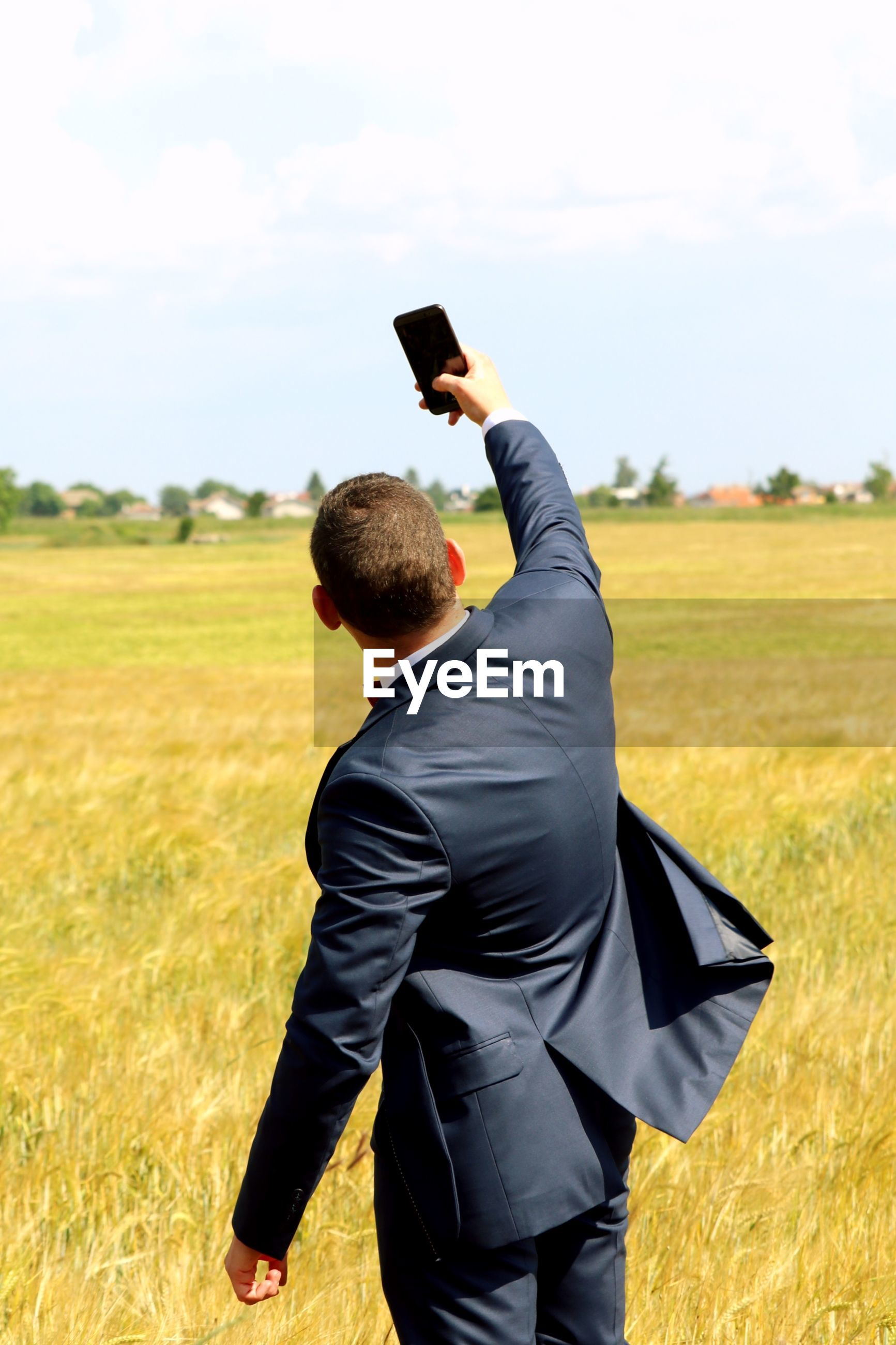 Rear view of man taking selfie while standing on field