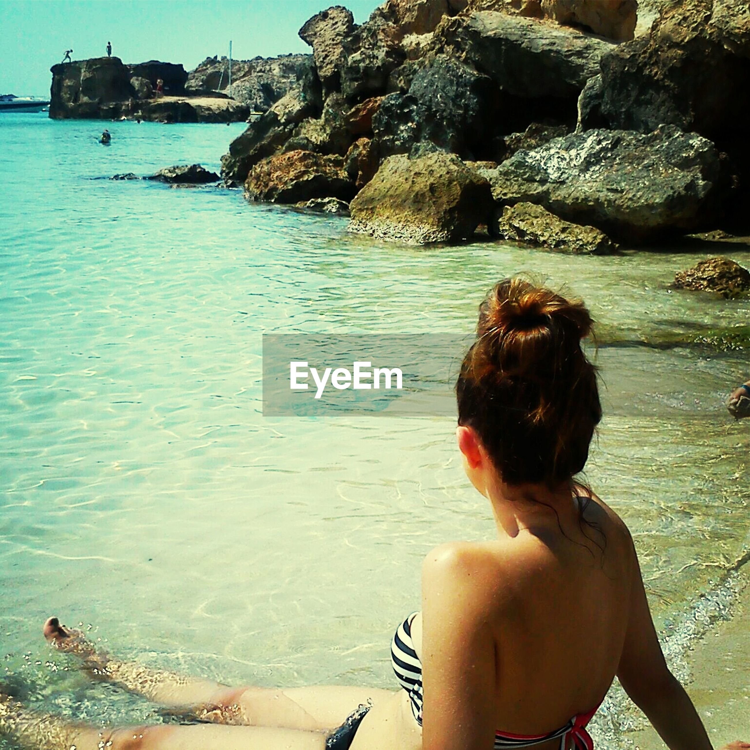water, sea, lifestyles, leisure activity, beach, vacations, person, shore, young adult, rear view, young women, shirtless, rock - object, weekend activities, sunlight, bikini, tourist, scenics