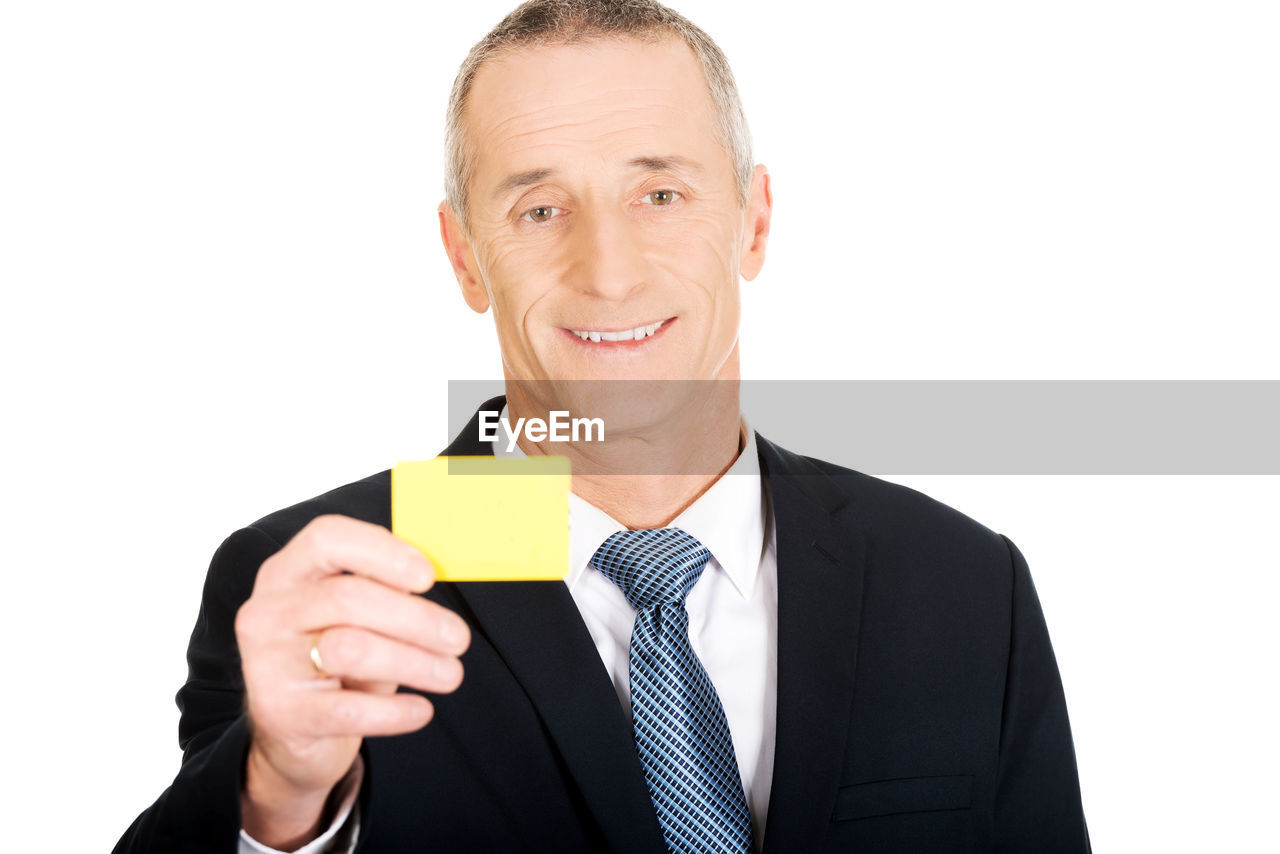 Portrait of smiling businessman holding business card against white background