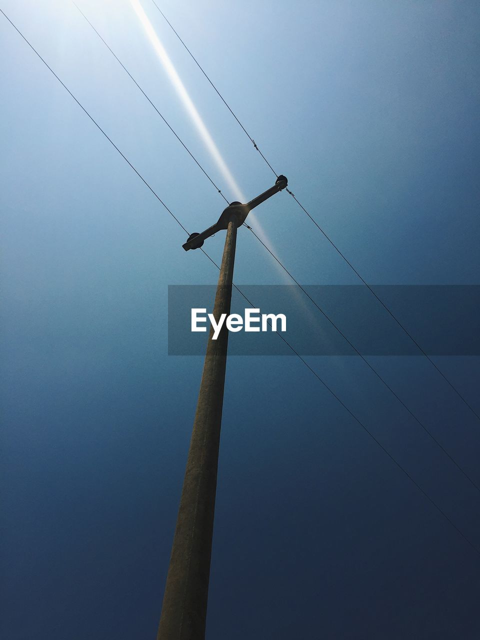 low angle view, sky, cable, electricity, fuel and power generation, technology, no people, connection, clear sky, nature, day, power supply, blue, electricity pylon, pole, power line, outdoors, environment, lighting equipment, telephone line, electrical equipment