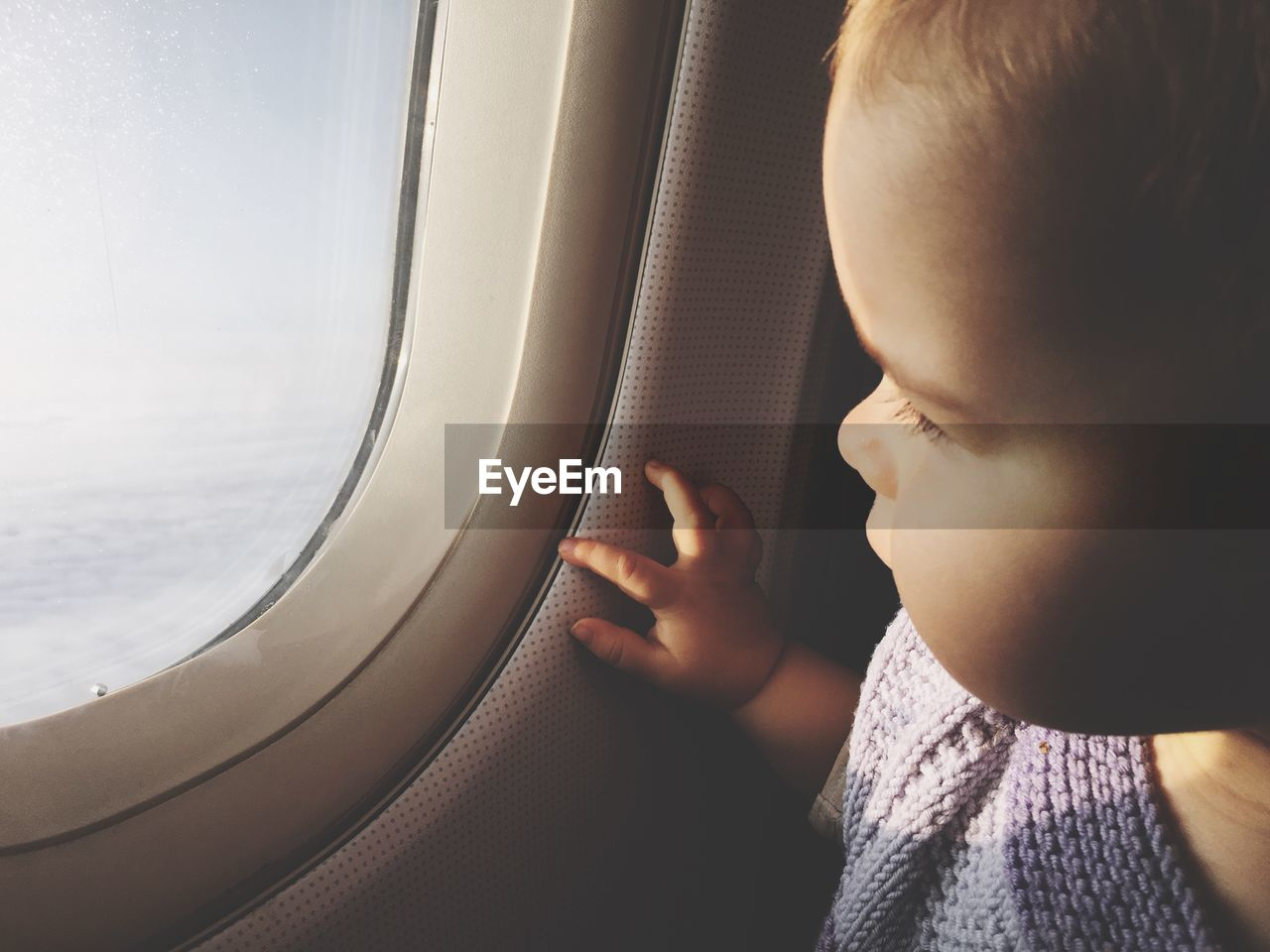 MIDSECTION OF BOY LOOKING AT AIRPLANE WINDOW