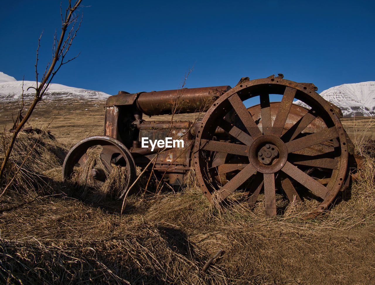 field, land, wheel, sky, nature, no people, transportation, clear sky, abandoned, plant, landscape, old, day, wagon wheel, outdoors, agriculture, tranquility, sunlight, grass, deterioration
