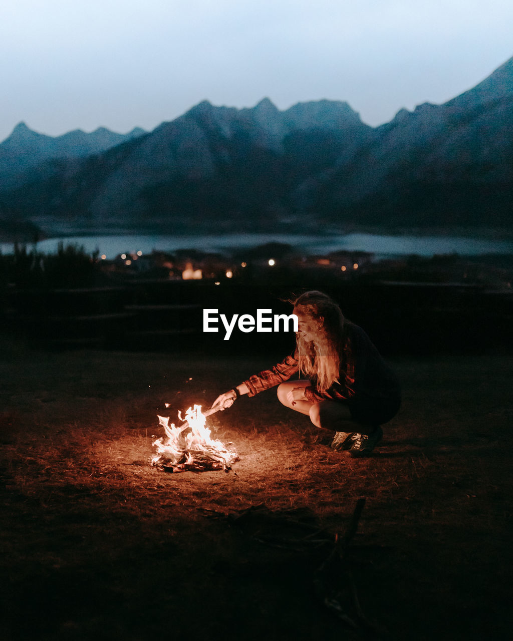 High angle view of hiker making a campfire by lake against mountain range