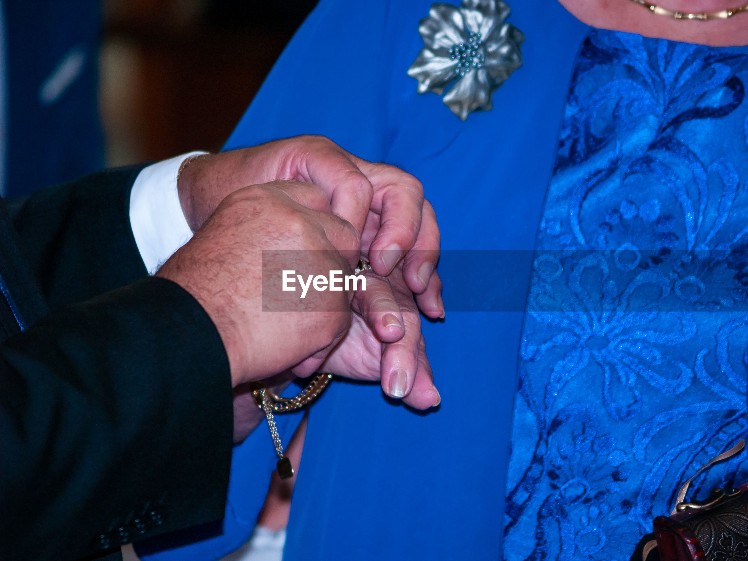 Cropped hands of man putting ring on bride finger