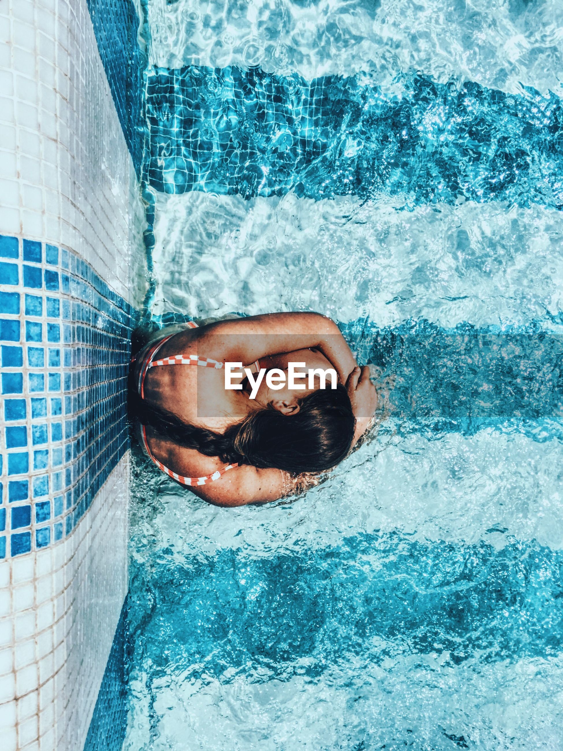 Overhead view of girl sitting in swimming pool