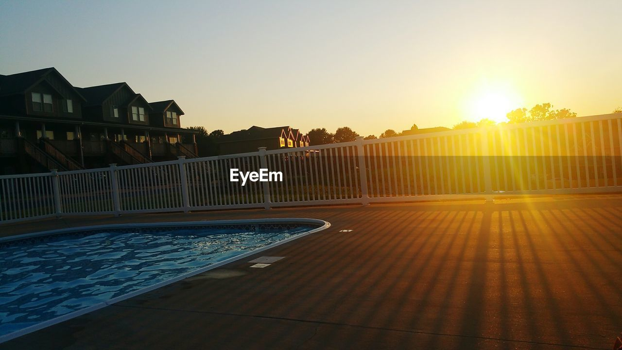 water, swimming pool, sunset, sun, sunlight, architecture, built structure, building exterior, outdoors, clear sky, no people, sky, nature, beauty in nature, day