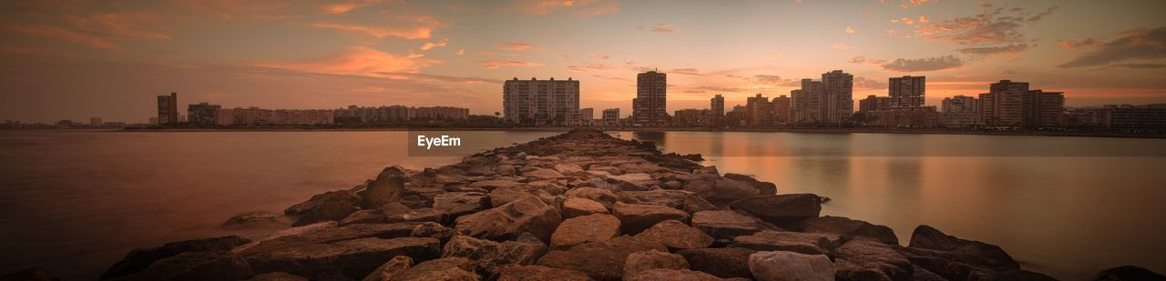 Panoramic View Of Groyne Over Sea Against Cityscape