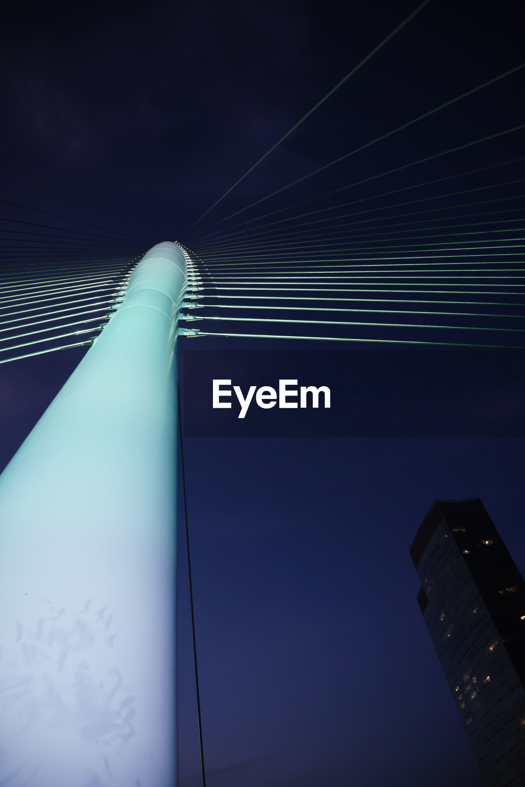 LOW ANGLE VIEW OF ILLUMINATED CABLES AGAINST BLUE SKY