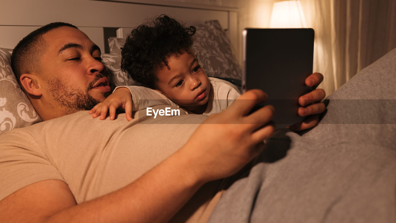Midsection of father and using mobile phone at home