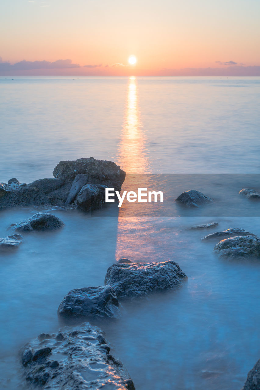 water, sunset, sea, sky, scenics - nature, beauty in nature, tranquility, tranquil scene, horizon, horizon over water, idyllic, rock, nature, solid, rock - object, no people, long exposure, motion, orange color, sun, outdoors, rocky coastline, flowing water