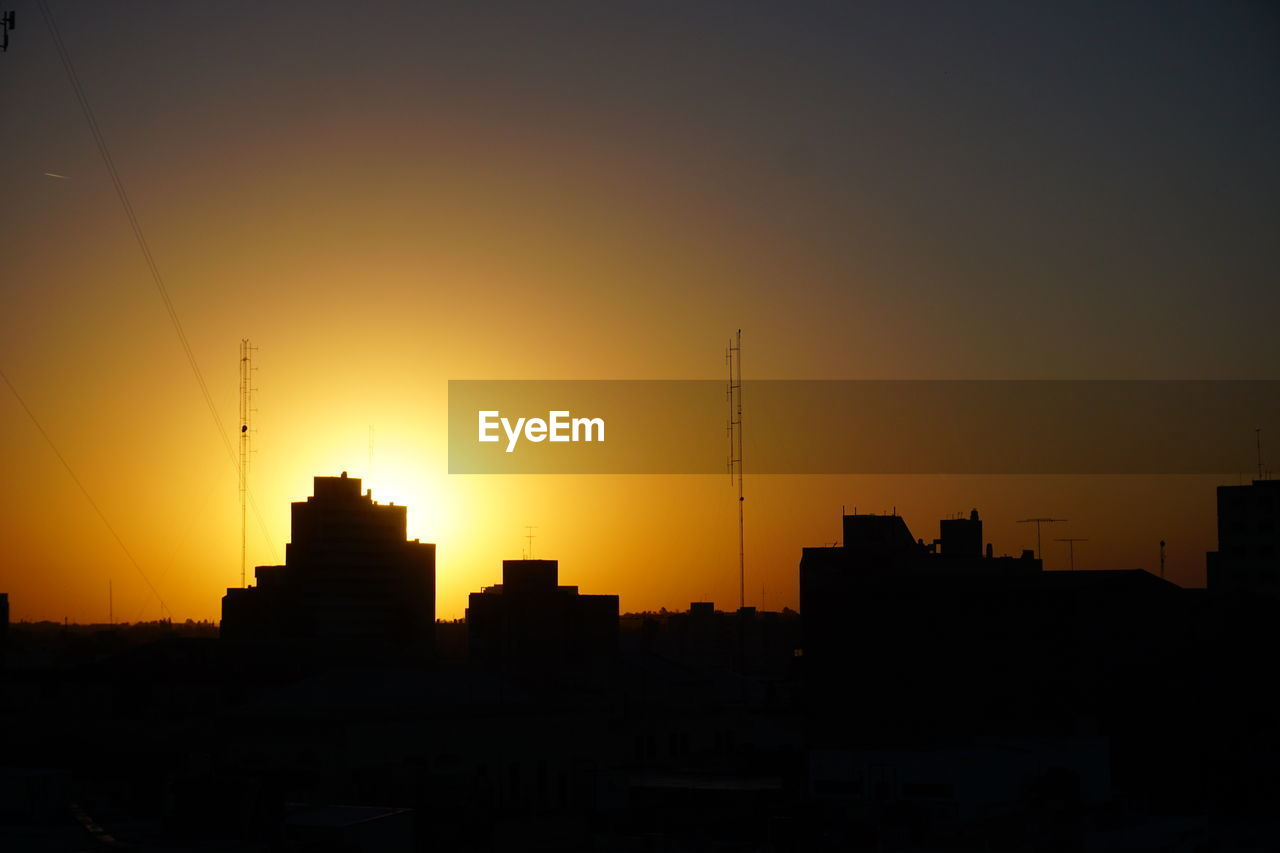 sunset, architecture, silhouette, building exterior, built structure, orange color, city, skyscraper, no people, development, sky, travel destinations, modern, outdoors, growth, cityscape, urban skyline, nature, clear sky, beauty in nature