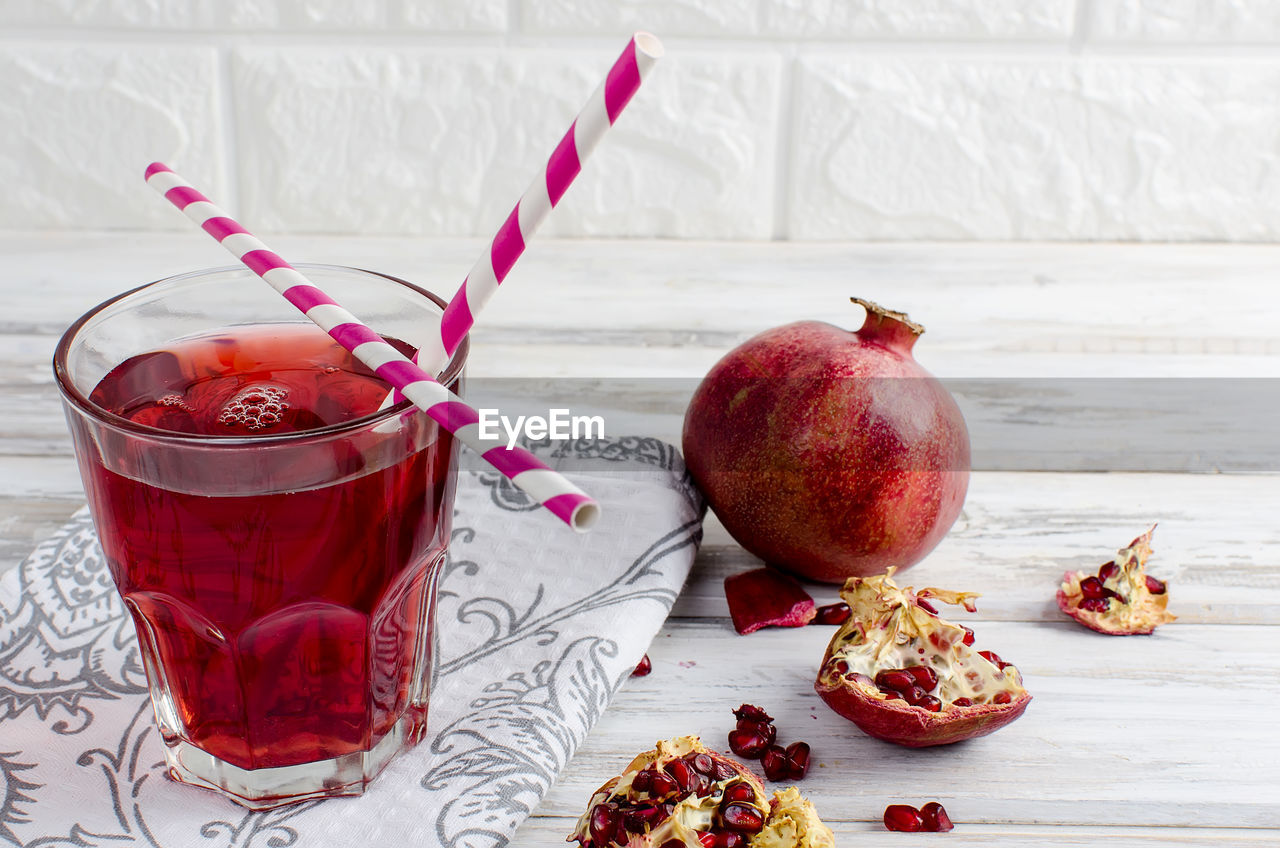 Close-up of juice by pomegranates in glass against wall on table