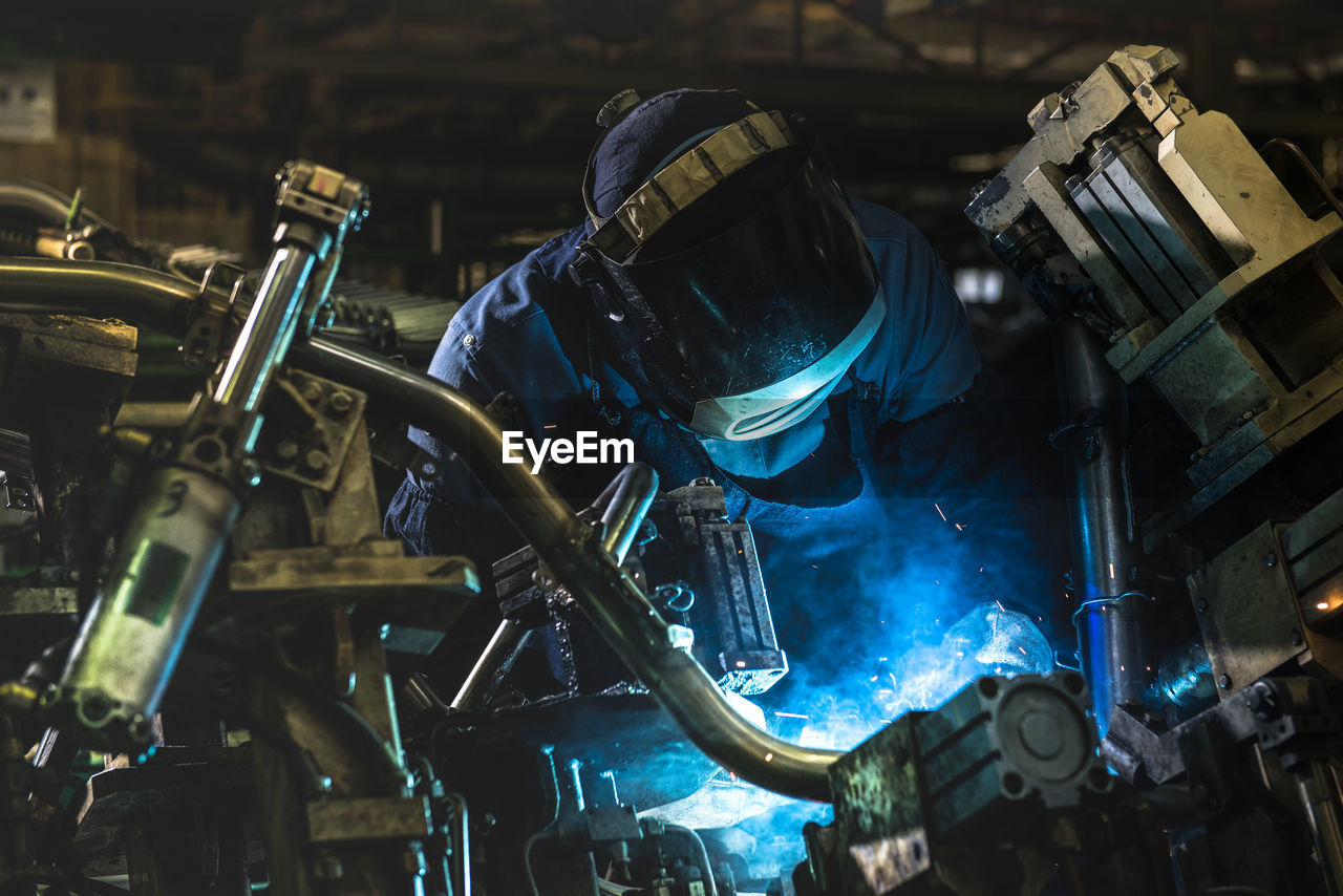 Worker Welding At Factory