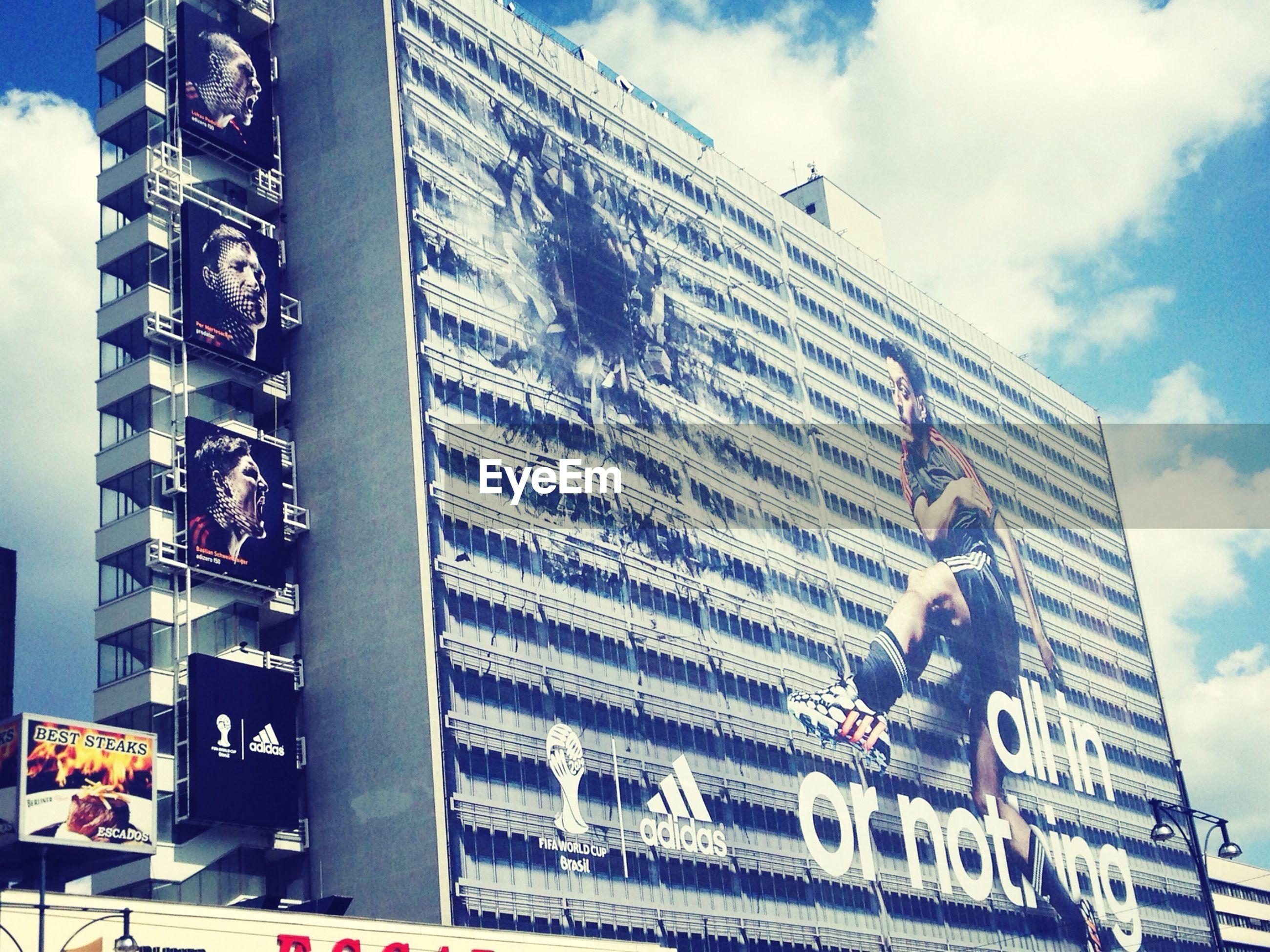 low angle view, architecture, building exterior, built structure, sky, city, building, modern, office building, city life, day, blue, outdoors, sunlight, text, western script, men, cloud - sky, cloud