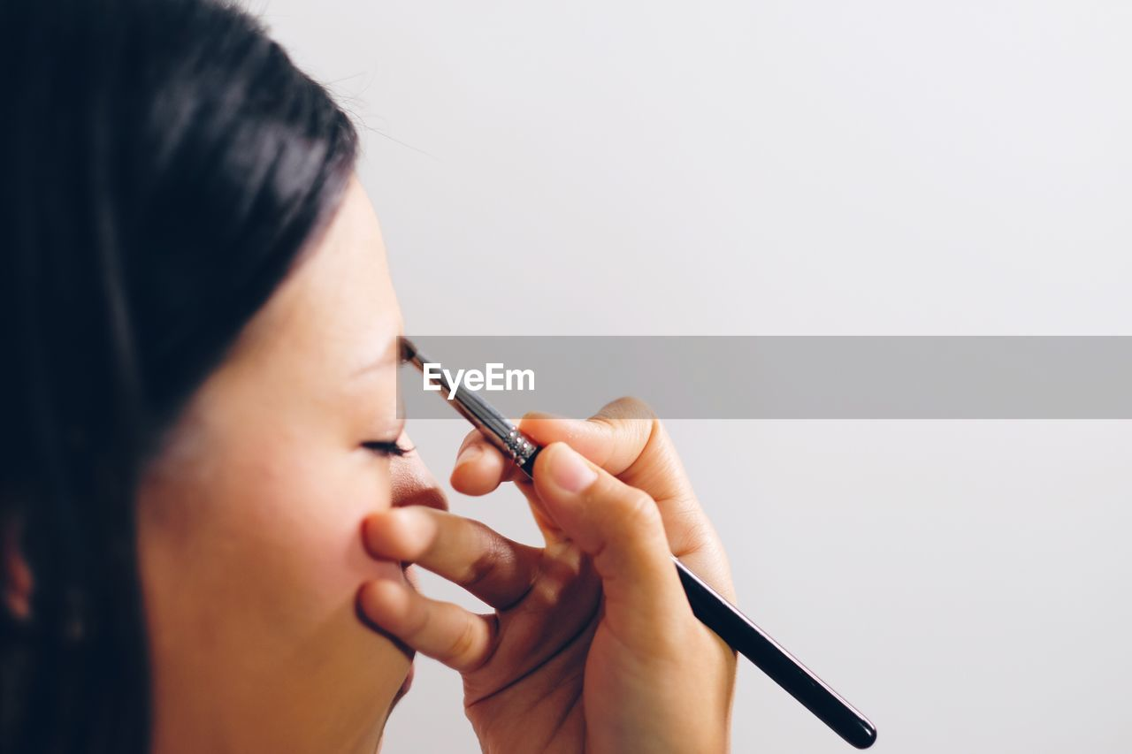 Close-Up Of Woman Applying Make-Up Against White Background