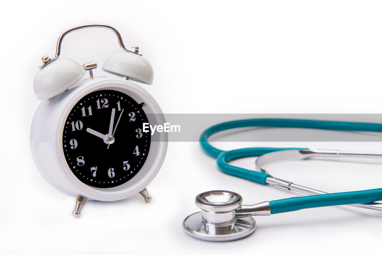 Close-up of alarm clock and stethoscope on white background